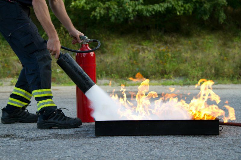 Firefighter using fire extinguisher to put out a fire